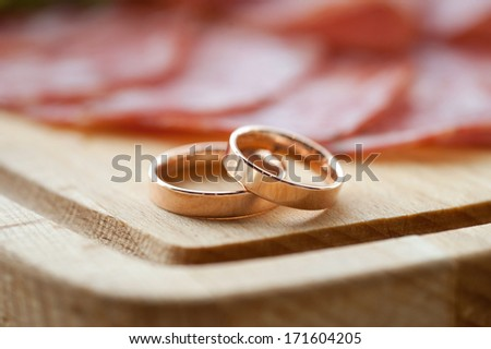 golden rings on wooden tray with wurst - stock photo