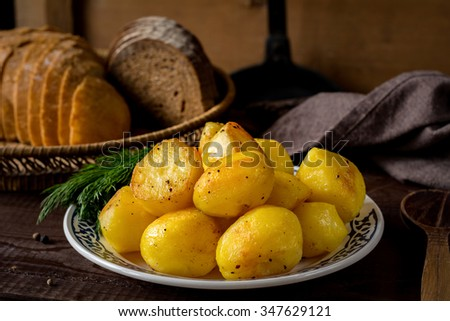 Golden roasted potatoes on plate garnished with ground black pepper and fresh dill, country style meal. Side dish for Christmas table - stock photo