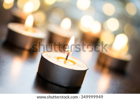 Golden Romantic Tealights In Bright Christmas Atmosphere On Wooden Table With Bokeh - Crooked Angle - stock photo