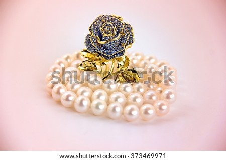 Golden rose brooch with pearls.