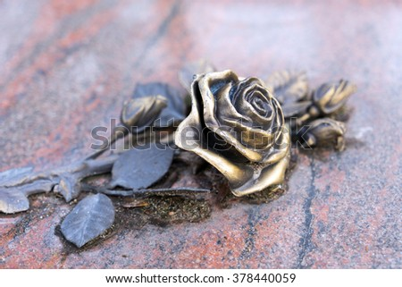 golden rose on a grave stone / Rose - stock photo