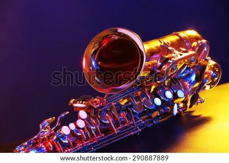 Golden saxophone on purple background - stock photo