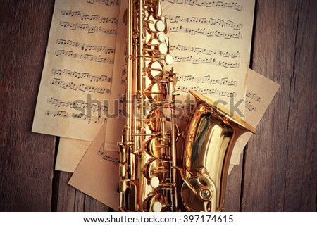 Golden saxophone with musical notes on wooden background, close up