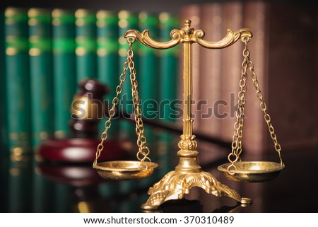 golden scale in front of judge's gavel and law books, justice concept - stock photo