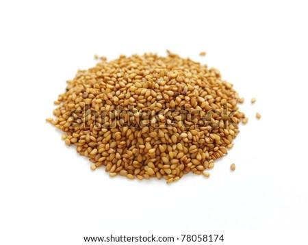 golden sesame seeds piled on white background - stock photo
