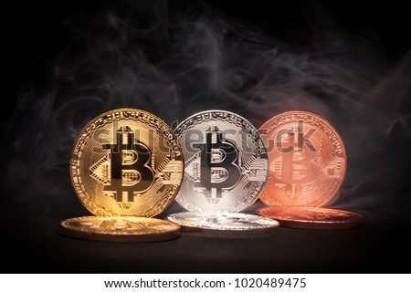 Golden, Silver and Bronze coloured Bitcoins with smoke