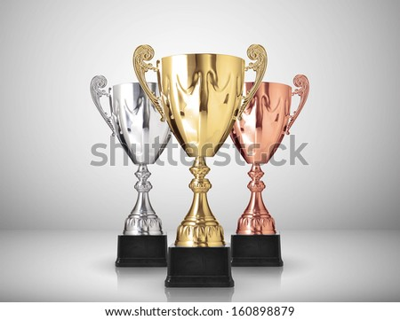 golden,silver and bronze trophies on gray background - stock photo