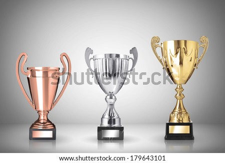 golden, silver and bronze trophies on gray background - stock photo