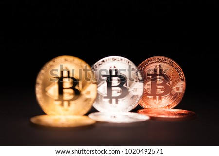 Golden, Silver and Copper Bitcoins over black, focussed on the Copper coin