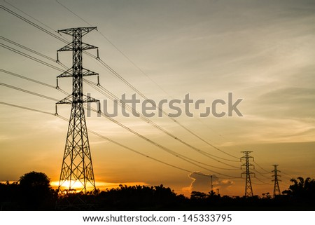 golden sky sunset with electric transmission tower and trees shadow - stock photo