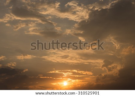 golden sky sunset with sun and black clouds - stock photo