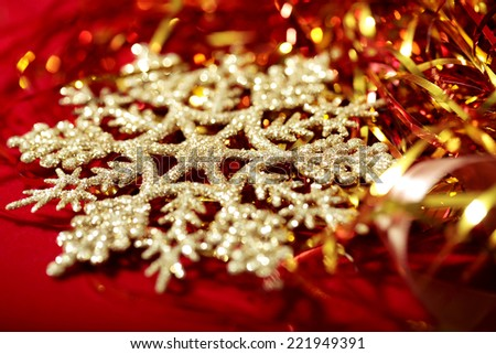 Golden snowflake and tinsel close-up on red christmas background  - stock photo