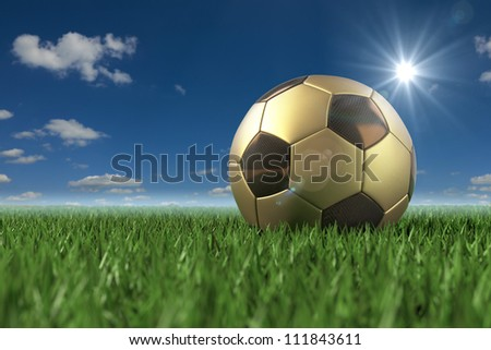 Golden Soccerball 3D on grass under blue sky - stock photo