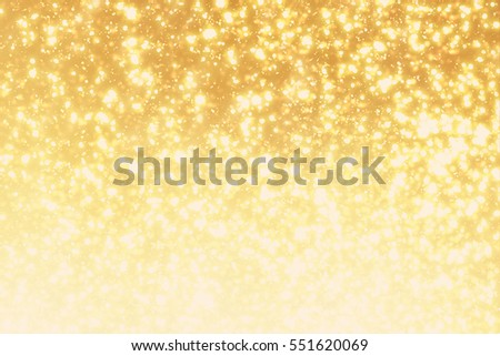 Golden sparkles or glitter lights. Festive gold background. Defocused circles bokeh or particles