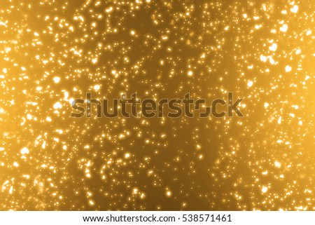 Golden sparkles or glitter lights. Merry Christmas festive background.defocused circle particles