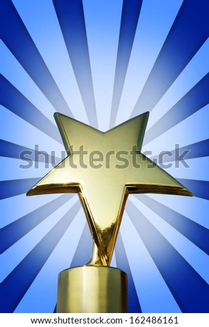 Golden star award on the stand against bright blue background - stock photo
