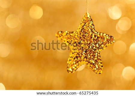 golden star decoration on blurred golden background - stock photo