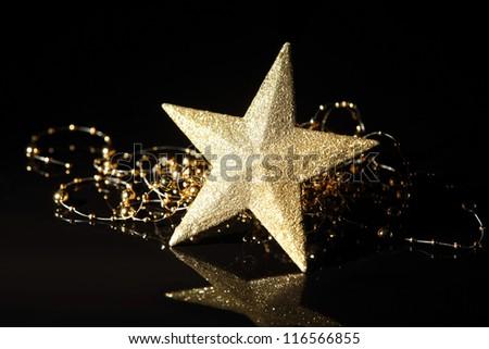 Golden star on black background. - stock photo