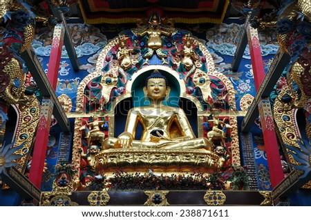 Golden statue of Gautam Buddha in Namdroling Monastery in Bylakuppe, Karnataka, India. - stock photo