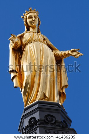 Golden Statue of Virgin Mary / Saint Mary / Our Lady in Lyon, France. Clear Blue Sky in the Background. - stock photo