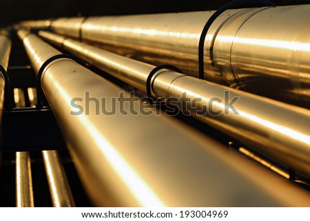golden steel pipeline during sunset - stock photo