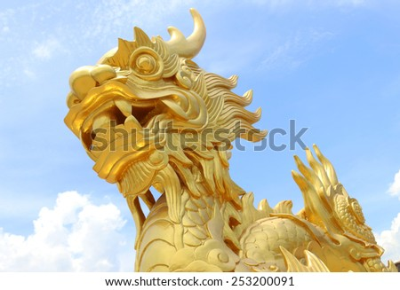 Golden stone dragon statue in Vietnam over blue sky - stock photo