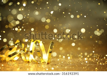 Golden streamers and glitter confetti,Closeup. - stock photo