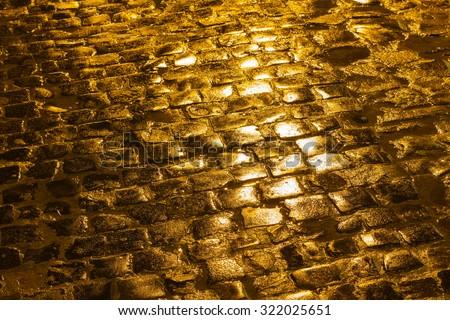 Golden street paving shining under evening lights - stock photo