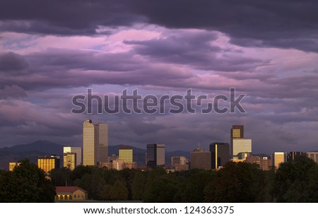 Golden sun reflected in downtown Denver buildings, under a purple and pink sky at sunrise.