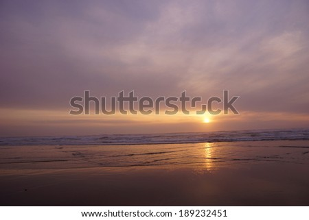 Golden sun setting on the Pacific Ocean  with surf and sea rocks,  near Yaquina Head, Newport, Oregon coast  - stock photo