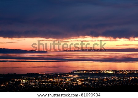 Golden sunlight peeks through dark storm clouds over the Pacific ocean and the city lights of Santa Barbara, California. - stock photo