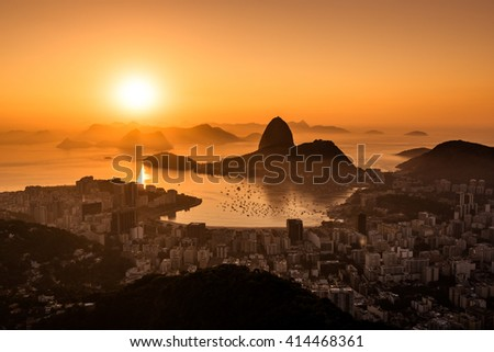Golden Sunrise over Guanabara Bay in Rio de Janeiro with Sugarloaf Mountain in the Horizon - stock photo