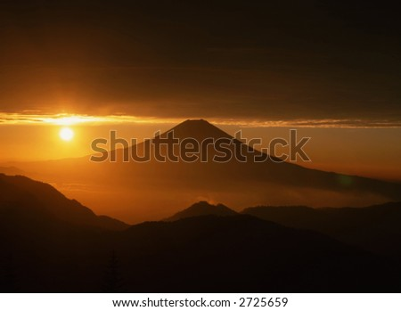 Golden sunrise over Mt. Fuji as viewed from an adjacent peak. - stock photo