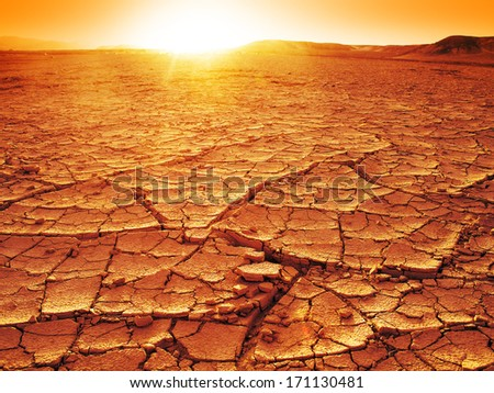 Golden sunset at a desert. Dry and thirsty soil. - stock photo