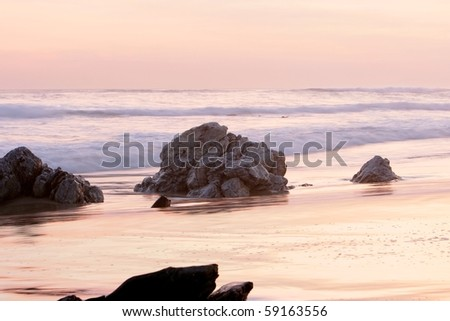 Golden sunset at South African coast with rock in foreground - stock photo
