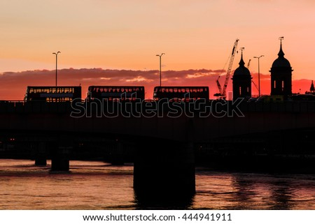 Golden sunset forming a silhouette of St. Paul, London Bridge and double deckers - stock photo