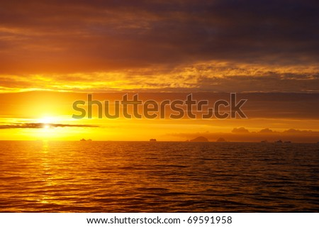 Golden sunset in antarctic sea. Shadows of icebergs on the horizon. - stock photo