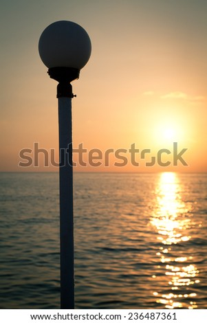Golden sunset on a sea with silhouette of a lantern - stock photo