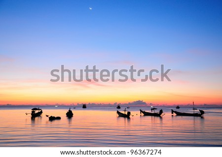 Golden sunset on a sea with silhouette of ships - stock photo
