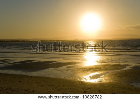 Golden sunset on the beach with dazzling reflections in the ocean surf at Byron Bay  on the north coast of New South Wales Australia