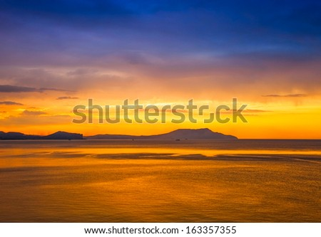 golden sunset on the sea and mountain view - stock photo