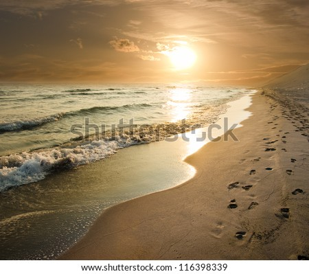 golden sunset on the sea shore and footprints in the sand - stock photo