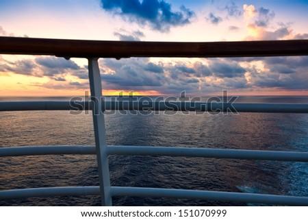 Golden sunset over the Caribbean Sea, through a ship's railing - stock photo