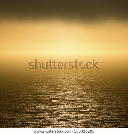 Golden sunset over the foggy Pacific Ocean. - stock photo