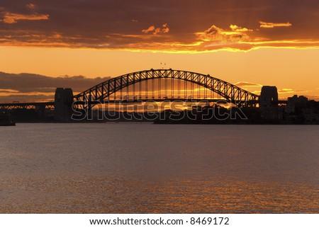 Golden sunset sky behind Sydney Harbor ( Harbour ) Bridge - a deep golden orange sunset just after the sun has gone down - stock photo
