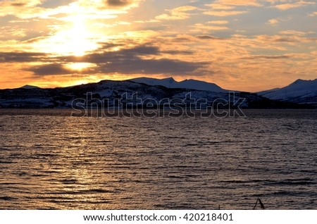 golden sunset sky over the Tromsoe city island