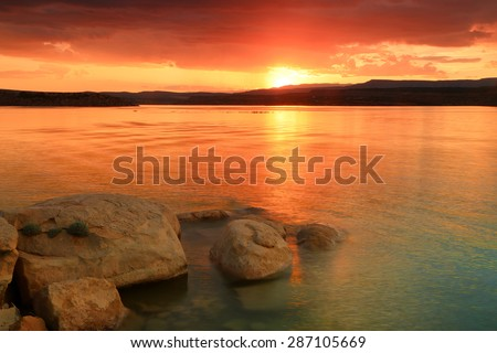 Golden sunset with rocks in a lake, Utah, USA. - stock photo