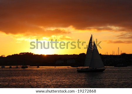 golden sunset with sailboat - stock photo