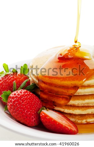 Golden syrup drizzling down over hot buttered pancakes with a strawberry garnish. - stock photo