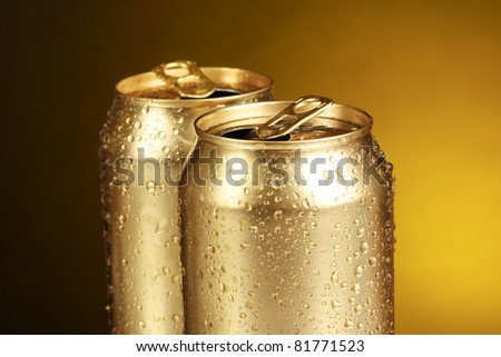 golden tin cans on yellow background - stock photo